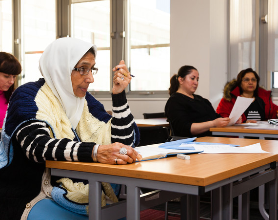 ESOL. female students listening to a lecture. ethnic mix